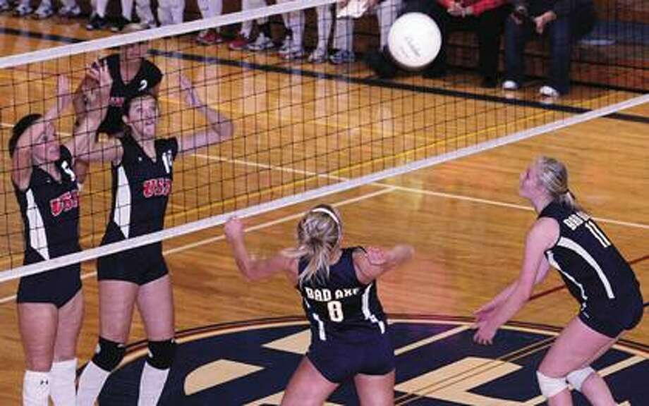 Bad Axe's Alison McVey (8) goes up for a kill over Unionville-Sebewaing Area's Andrea Vermeersch (5) and Miranda Fuerst (14) during Game 2 of the Class C district quarterfinals Tuesday night. The Patriots beat the Hatchets in five games.