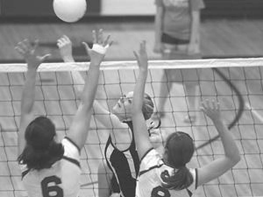 Bad Axe's Samantha Breault battles at the net with Cass City's Ashleigh Moore (6) and Logan Rowell (8).
