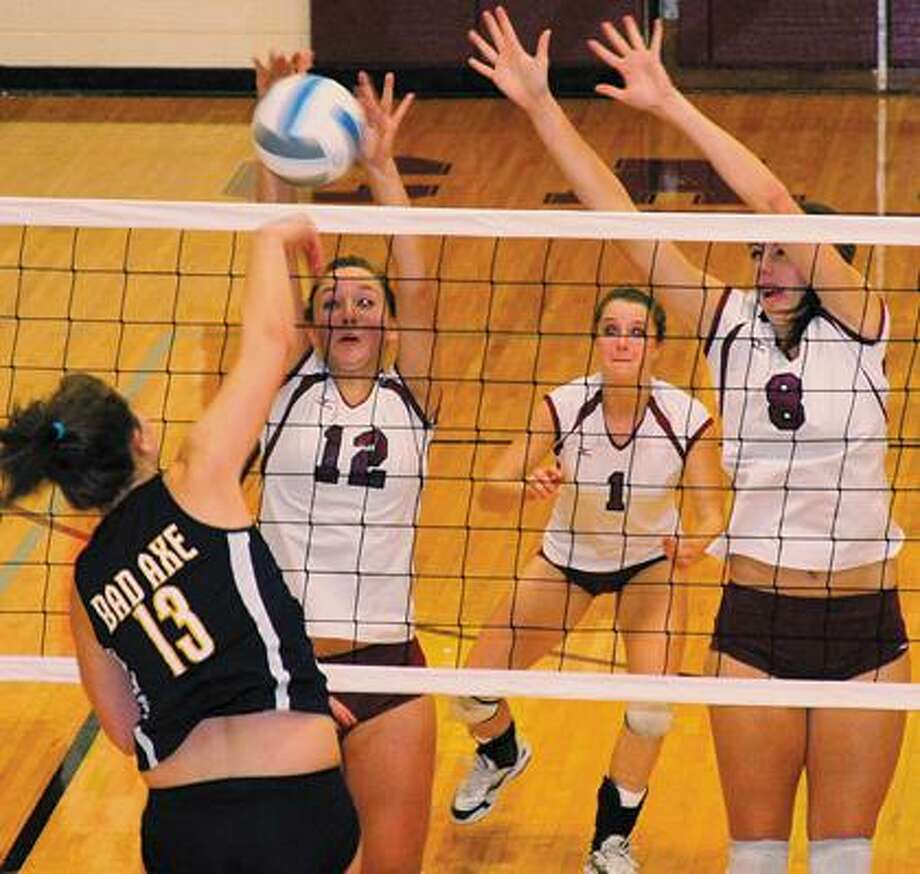 Bad Axe's Taylor Breault hammers down a kill against Cass City's trio of defenders — Carley Hendrick (12), Stephanie Leeson (1) and Logan Rowell (8). Breault led the Hatchets with 10 kills in the match.