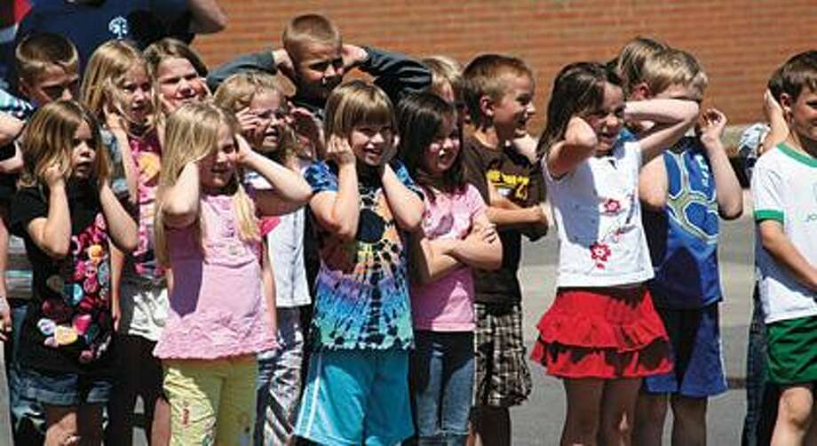 Students cover their ears as an EMT turns on the sirens.