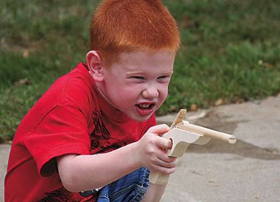 Evan Rice, 4, takes aim with a toy rubberband shooter.
