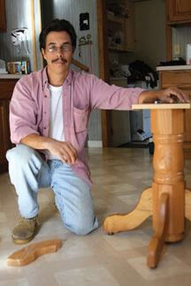 Daniel Velasco, of Bad Axe, shows off a table from Sean Penn's trailer he fixed after someone broke two of its legs.