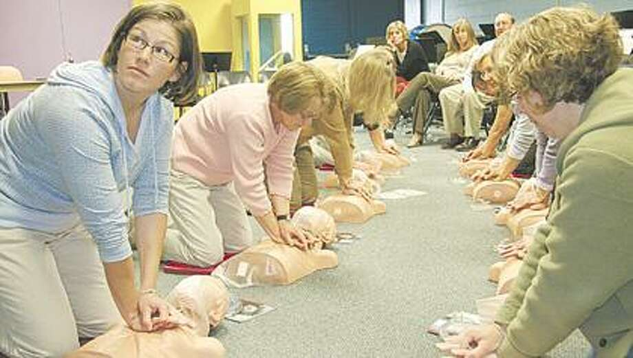 Pictured is Bad Axe Junior High School Teacher Kelly Seltz, front left, practicing on a CPR mannequin along side her fellow co-workers.