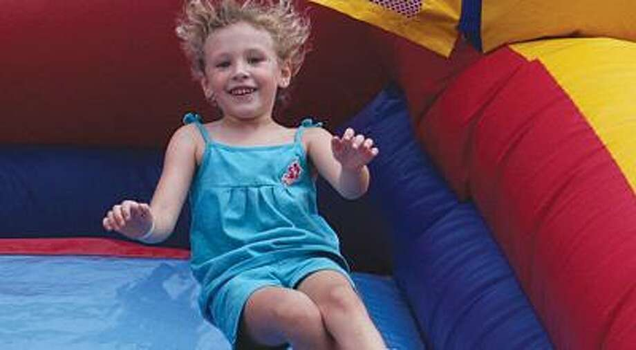 Lupita Young, 5, of Port Austin enjoys the inflatable slide