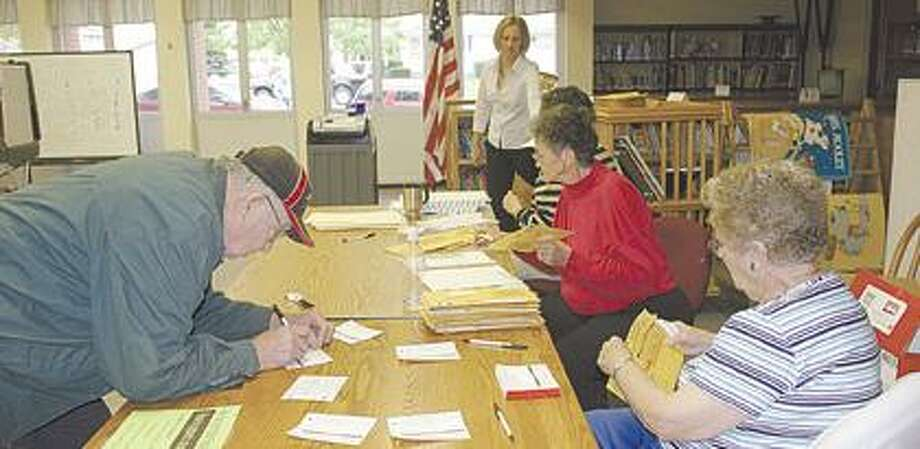 Owendale-Gagetown Area School District election workers help a district resident go through the voting process. From the back, the workers are Amy Lowman (standing), Mary Marker, Hilda Koch and Jackie Goodell.