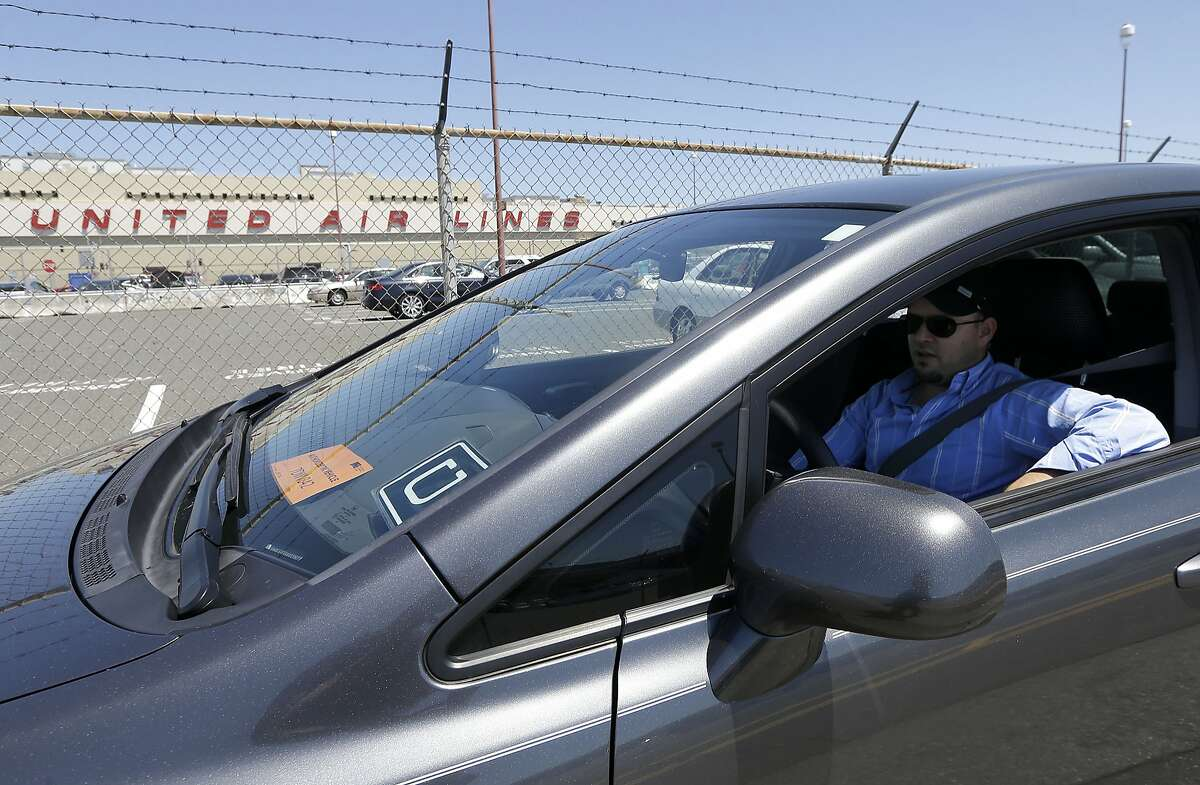 Uber driver Karim Amrani sits in his car near the San Francisco International Airport parking area in this July 15, 2015 photo. A judge on Thursday rejected a $100 million settlement between the ride-hailing service and drivers who wanted to be classified as employees. (AP Photo/Jeff Chiu)