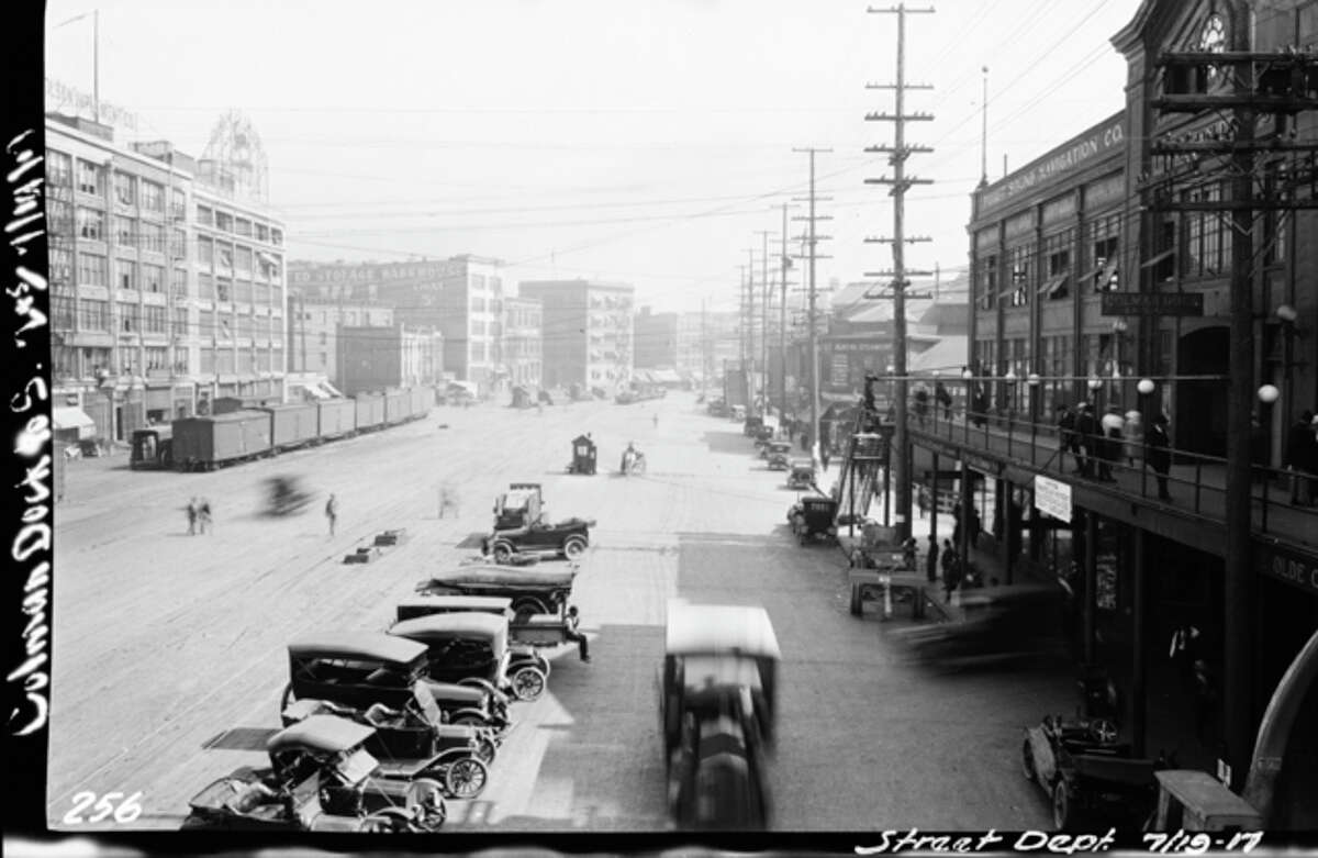 This 1917 photo shows Railroad Avenue (now Alaskan Way) looking south from what is likely the Marion Street walkway to Colman Dock (the terminal building is seen on the right). Photo courtesy Seattle Municipal Archives.