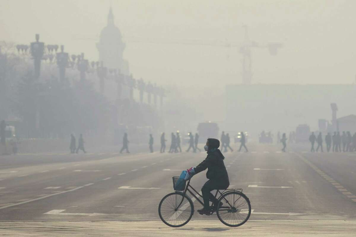 A woman wearing a mask as she rides her bicycle in December along a street near Tiananmen Square on the third day of a