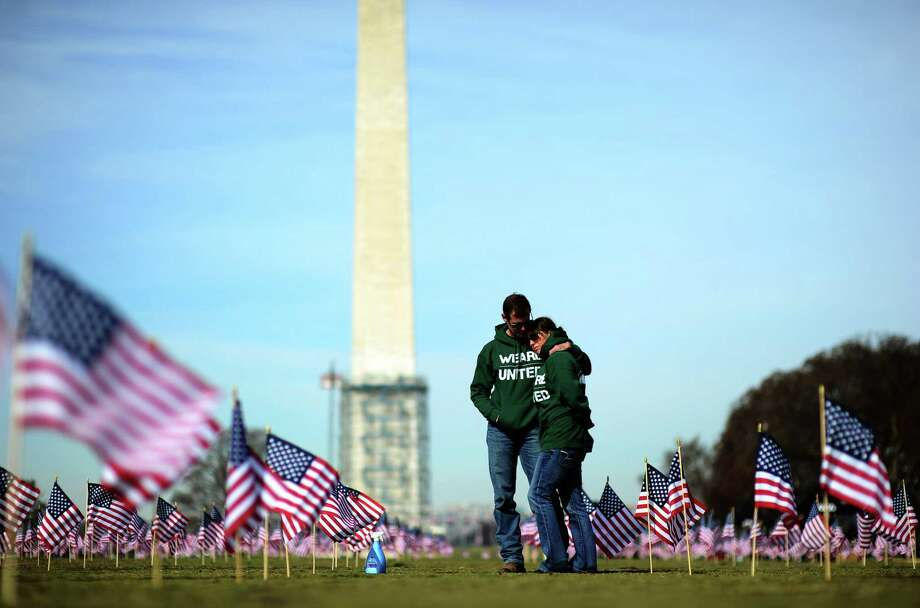 Veterans Jeff Hensley and Colleen Ryan helped set up 1,892 American flags on the National Mall in Washington, D.C., on March 27, 2014. The display, organized by the Iraq and Afghanistan Veterans of America, represented each one of the active-duty and former service members who had died by suicide up to that point in 2014. Photo: JEWEL SAMAD /AFP /Getty Images / AFP