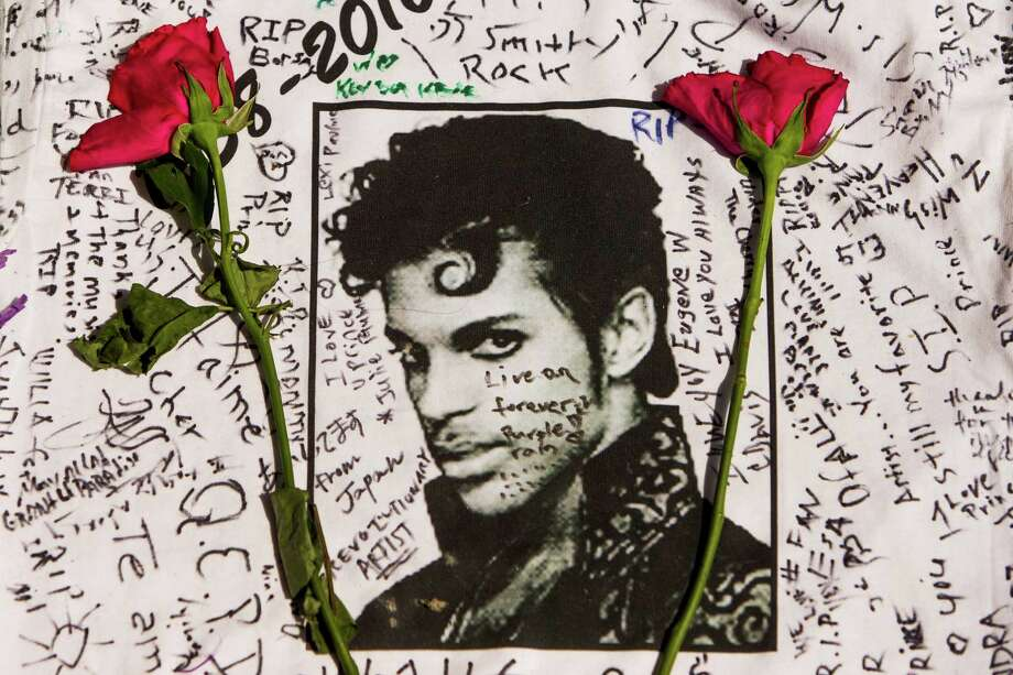 Flowers lay on a T-shirt signed by fans of singer Prince at a makeshift memorial place created outside Apollo Theatre in New York, Friday, April 22. Photo: Andres Kudacki, Associated Press / FR170905 AP
