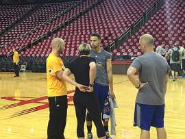 Warriors guard Stephen Curry talks to team trainers Thursday in Houston.