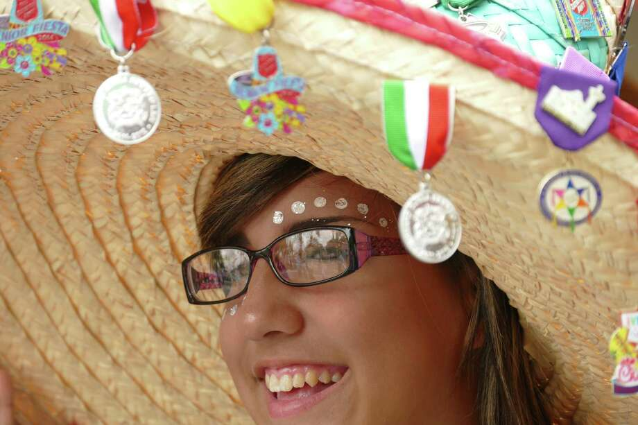 Brianna Del Toro wears a sombrero adorned with Fiesta medals during the Piñatas in the Barrio event at Plaza Guadalupe on Saturday, April 16, 2016. The official Fiesta event raised funds to support projects and scholarships on the West Side. Photo: Billy Calzada, Staff / San Antonio Express-News / San Antonio Express-News