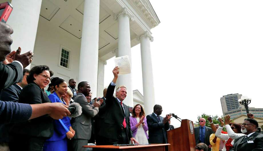 Gov. Terry McAuliffe holds up the order he signed to restore rights to felons in Virginia. Photo: Mark Gormus, MBI / Richmond Times-Dispatch
