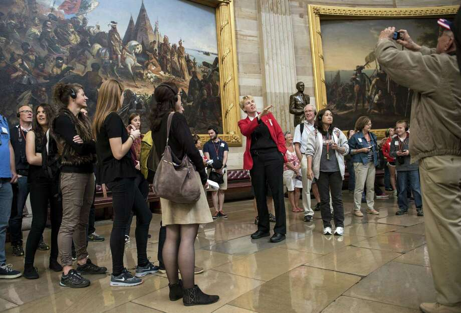 Tourists listen to a tour guide speak in the Rotunda of the US Capitol Building on Capitol Hill. Photo: BRENDAN SMIALOWSKI, Staff / 2013 Brendan Smialowski