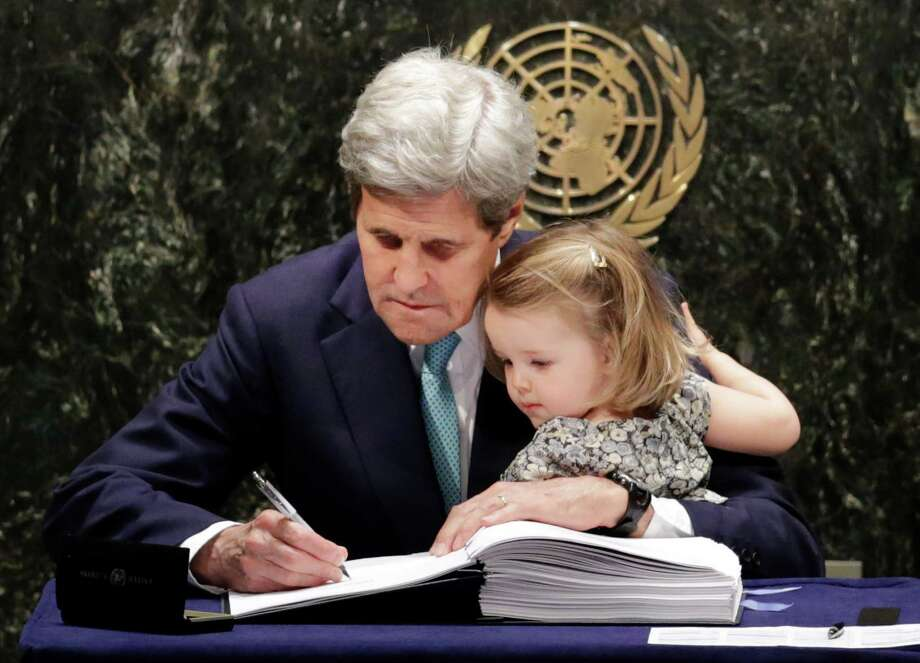 U.S. Secretary of State John Kerry holds his granddaughter, Isabel Dobbs-Higginson, as he signs the Paris Agreement Friday at U.N. headquarters.  Photo: Mark Lennihan, STF