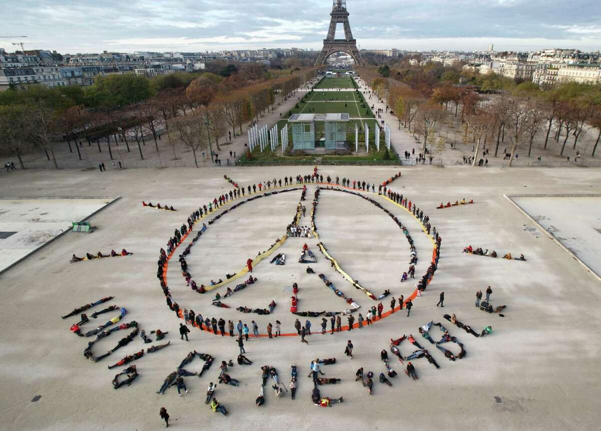 FILE - In this Dec. 6, 2015 file photo, environmentalist activists form a human chain representing the peace sign and the spelling out