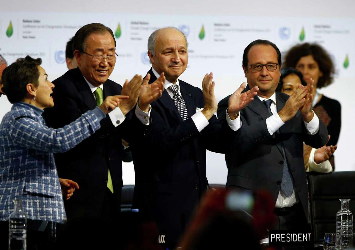FILE - In this Dec. 12, 2015 file photo, French President Francois Hollande, right, French Foreign Minister and president of the COP21 Laurent Fabius, second, right, United Nations climate chief Christiana Figueres and United Nations Secretary General Ban ki-Moon applaud after the final conference at the COP21, the United Nations conference on climate change, in Le Bourget, north of Paris. Governments have adopted a global agreement that for the first time asks all countries to reduce or rein in their greenhouse gas emissions. Four months after negotiating a global climate agreement in Paris, government officials are coming to New York on Friday, April 22, 2016, to sign the pact in a ceremony at the United Nations. (AP Photo/Francois Mori)