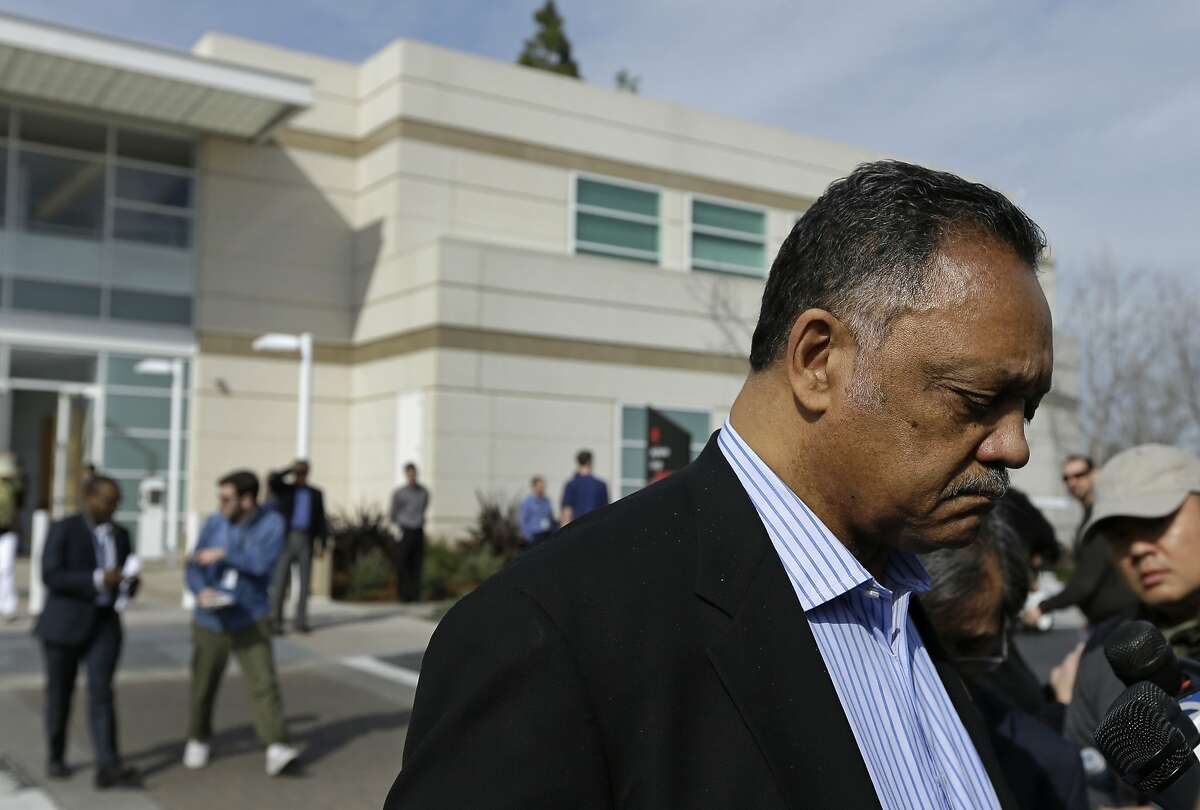 Civil rights activist Jesse Jackson, right, speaks to reporters after attending the Apple annual shareholder meeting Friday, Feb. 26, 2016, at Apple headquarters in Cupertino, Calif. Apple CEO Tim Cook defended his company's opposition to the FBI's iPhone-hacking plan at the company's annual shareholder meeting, one day after the tech giant formally challenged a court order to help the FBI unlock an encrypted iPhone used by a murderous extremist in San Bernardino,Calif. (AP Photo/Ben Margot)