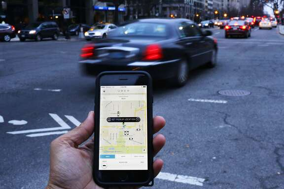 (FILES) This file photo taken on March 25, 2015 shows an UBER application as cars drive by in Washington, DC.  Uber has agreed to pay up to $100 million to settle two class action suits filed by drivers who said they were employees entitled to benefits, rather than independent contractors. The suits were filed in California and Massachusetts. In the California case, a judge had approved the class action suit and was set to rule on it in June 2016.  / AFP PHOTO / Andrew Caballero-ReynoldsANDREW CABALLERO-REYNOLDS/AFP/Getty Images