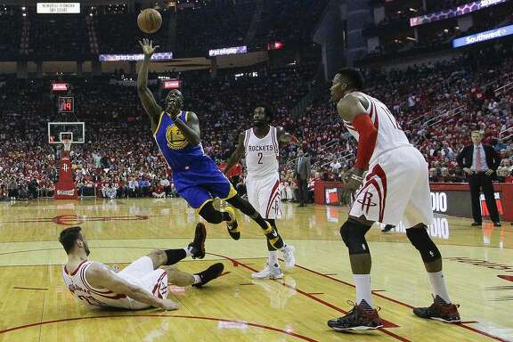Golden State Warriors forward Draymond Green (23) takes a shot after knocking Houston Rockets forward Donatas Motiejunas (20) to the ground during the first half in game three of a first-round NBA Playoffs series at Toyota Center Thursday, April 21, 2016 in Houston. ( Karen Warren / Houston Chronicle )