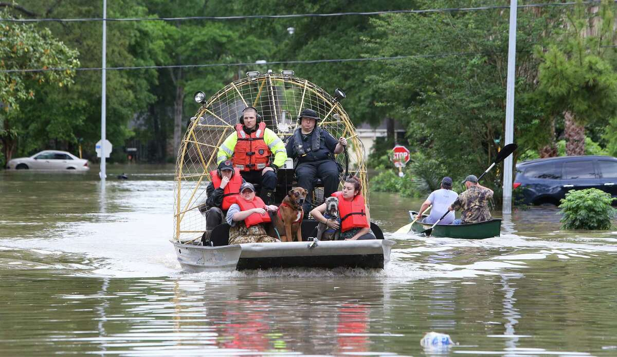 Harris County Sheriff's deputies rescue residents and pets from their homes Wednesday near Nanes and Baltic in the Cypress area.