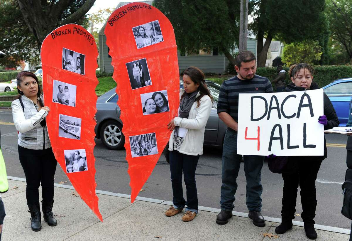 Proponents of Presidential executive action on immigration to include parents along with Deferred Action for Childhood Arrivals (DACA) demonstrate outside a rally with First lady Michelle Obama Thursday, Oct. 30, 2014, at Wilbur Cross High School in New Haven, Conn.