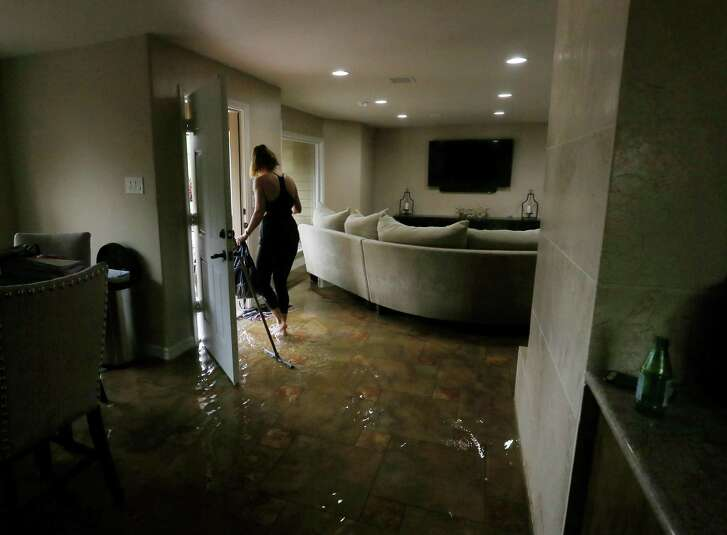 Meital Harari cleans water out of her Meyerland home, Monday, April 18, 2016, in Houston. Her family rode out the storm at a nearby house because her daughter has nightmares from the Memorial Day floods.  ( Jon Shapley / Houston Chronicle )