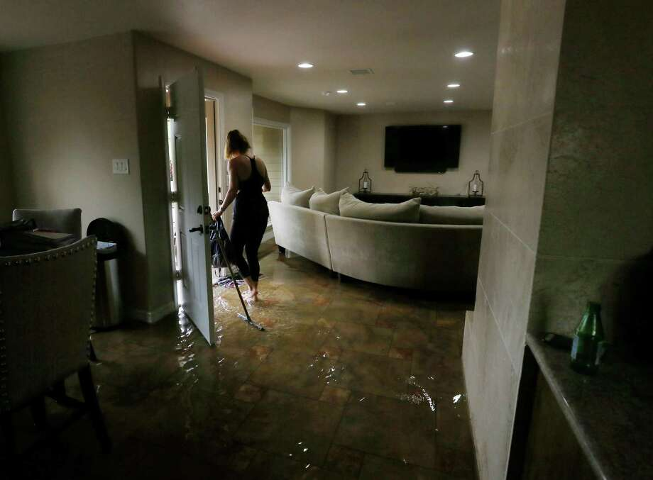 Meital Harari cleans water out of her Meyerland home, Monday, April 18, 2016, in Houston. Her family rode out the storm at a nearby house because her daughter has nightmares from the Memorial Day floods.  ( Jon Shapley / Houston Chronicle ) Photo: Jon Shapley, Staff / © 2015  Houston Chronicle