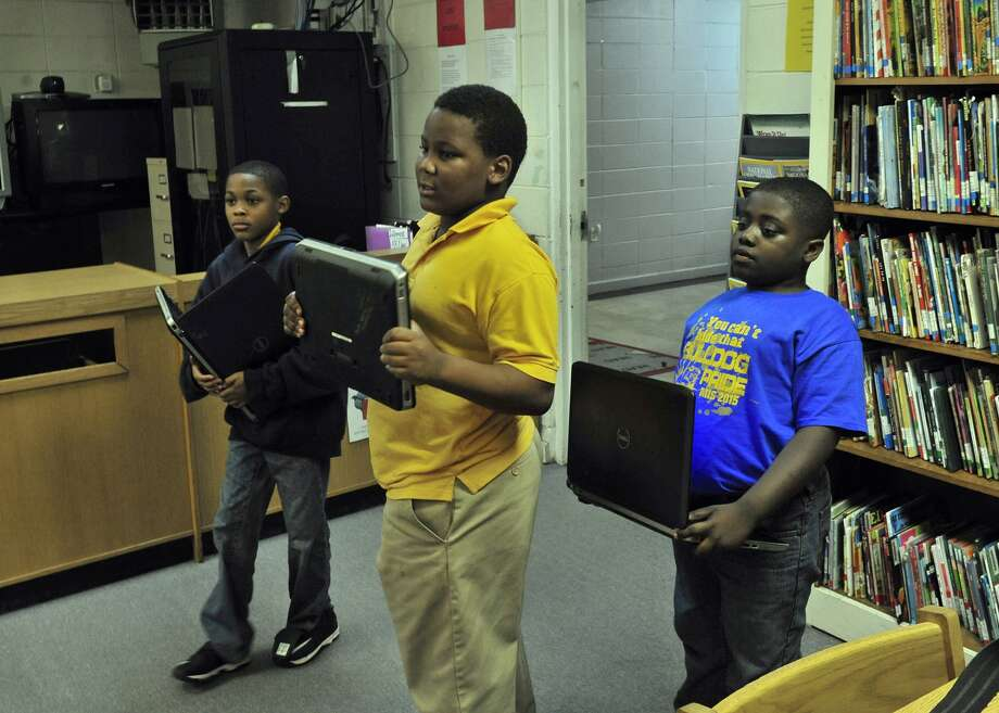 Jarquiese McCaskey, Jaquan Hawkins and Zaylan Randolph hope for a good Internet day at Monroe Intermediate School in Alabama. Photo: Michael S. Williamson, Washington Post