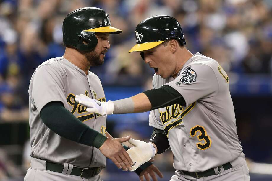 Oakland Athletics' Chris Coghlan (3) celebrates his three-run home run with teammate Yonder Alonso during the second inning of a baseball game against the Toronto Blue Jays on Friday, April 22, 2016, in Toronto. (Frank Gunn/The Canadian Press via AP) Photo: Frank Gunn, Associated Press