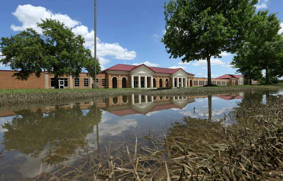 Cy-Fair High School still had pooled floodwater on Friday. Cy-Fair ISD saw 53 campuses damaged by the storm, but may only have to pay the $100,000 deductible if insurance approves the claims. Photo: Jon Shapley, Staff / © 2015  Houston Chronicle