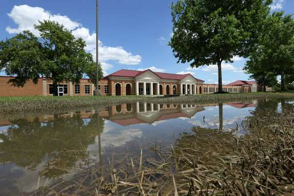 Cy-Fair High School still had pooled floodwater on Friday. Cy-Fair ISD saw 53 campuses damaged by the storm, but may only have to pay the $100,000 deductible if insurance approves the claims.