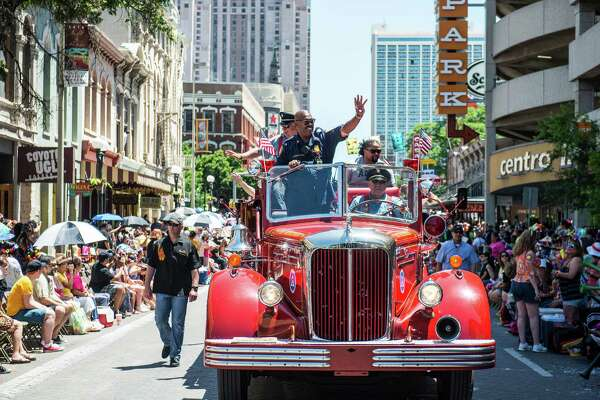 San Antonio Fire Chief Charles Hood waves to the crowds during the Battle of Flowers parade in San Antonio, Texas on Friday, April 22, 2016.