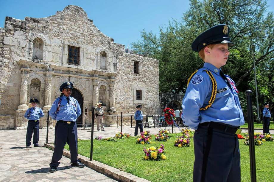 Members of the San Antonio Academy place flowers in front of The Alamo as a remembrance of those who died at the battles of the Alamo and San Jacinto during the Battle of Flowers parade in San Antonio, Texas on Friday, April 22, 2016. Photo: Matthew Busch, Stringer / © Matthew Busch
