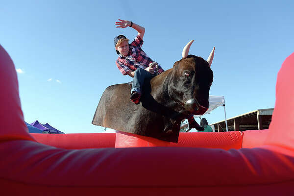 Joshua Haltom, 13, of Beaumont takes a ride on his family's mechanical bull ride as they await festival-goers at the Texas Bar B Que Festival Friday night in Vidor. Festival goers can take in the IBCA sanctioned barbecue cook-off, enjoy musical entertainment, carnival rides, games and children's activities throughout the weekend as the festival continues through Sunday in Conn Park. Photo taken Friday, April 22, 2016 Kim Brent/The Enterprise