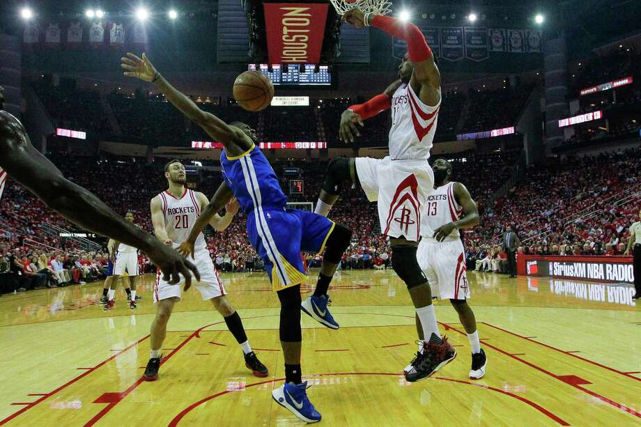 In what appears to be basketball ballet, Rockets center Dwight Howard, right, rejects a shot attempt by Warriors center Festus Ezeli, left, during the first half of the Rockets' victory Thursday night. Photo: Michael Ciaglo, Staff / © 2016  Houston Chronicle