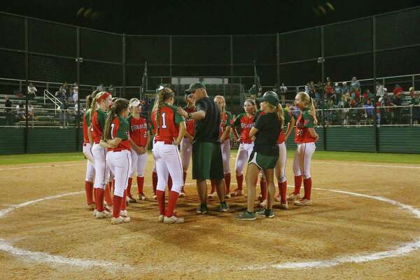Head Coach Tim Borths pats Leah Starkweather, leftfielder, on the shoulder as the team huddles following a loss to the Kingwood Mustangs, at The Woodlands High School, Friday, April 22, 2016, in The Woodlands.