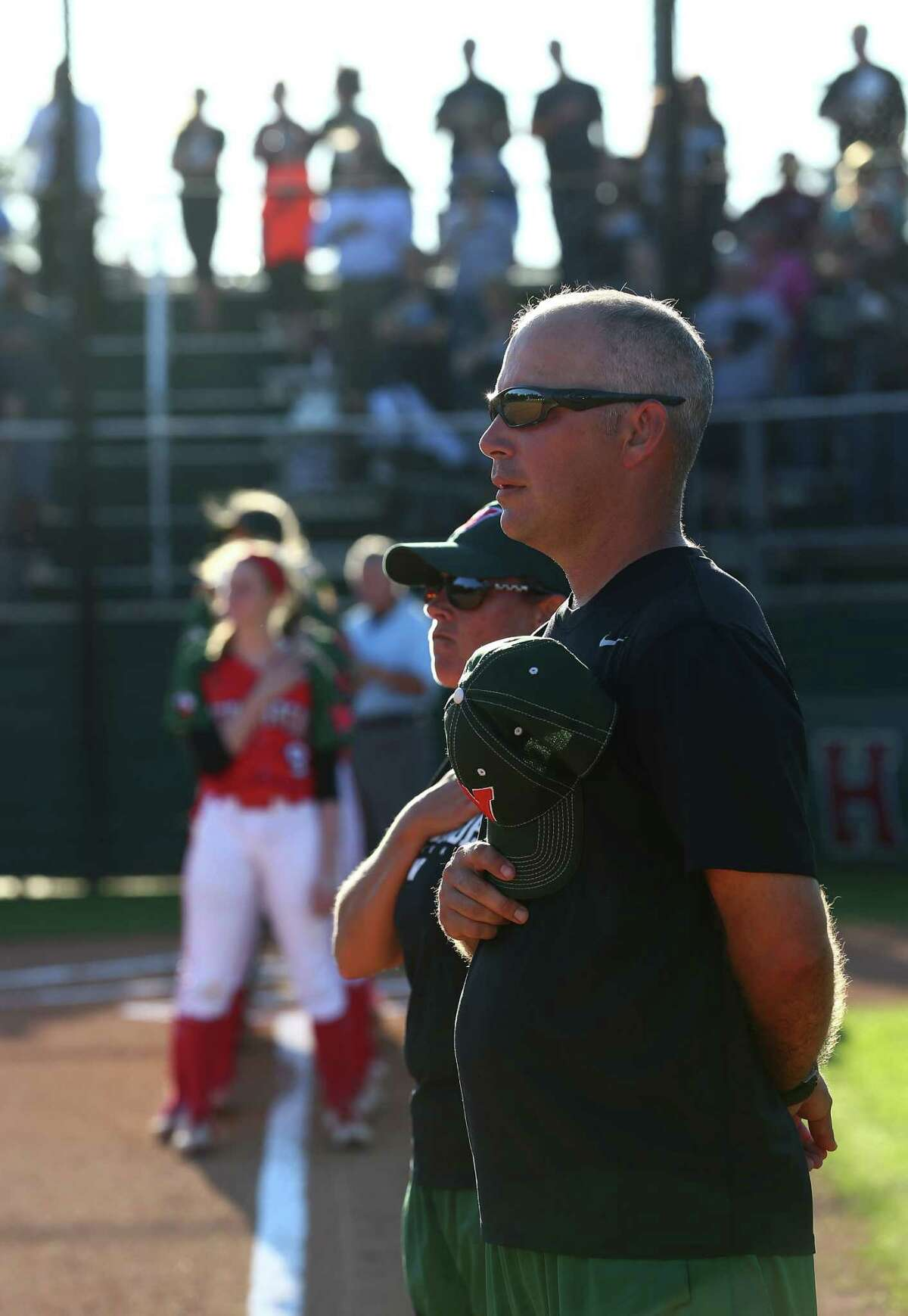 Head Coach Tim Borths, right, and Assistant Coach Paula Miller listen as the National Anthem is played before a softball game between the Woodlands Lady Highlanders and the Kingwood Mustangs, at The Woodlands High School, Friday, April 22, 2016, in The Woodlands.