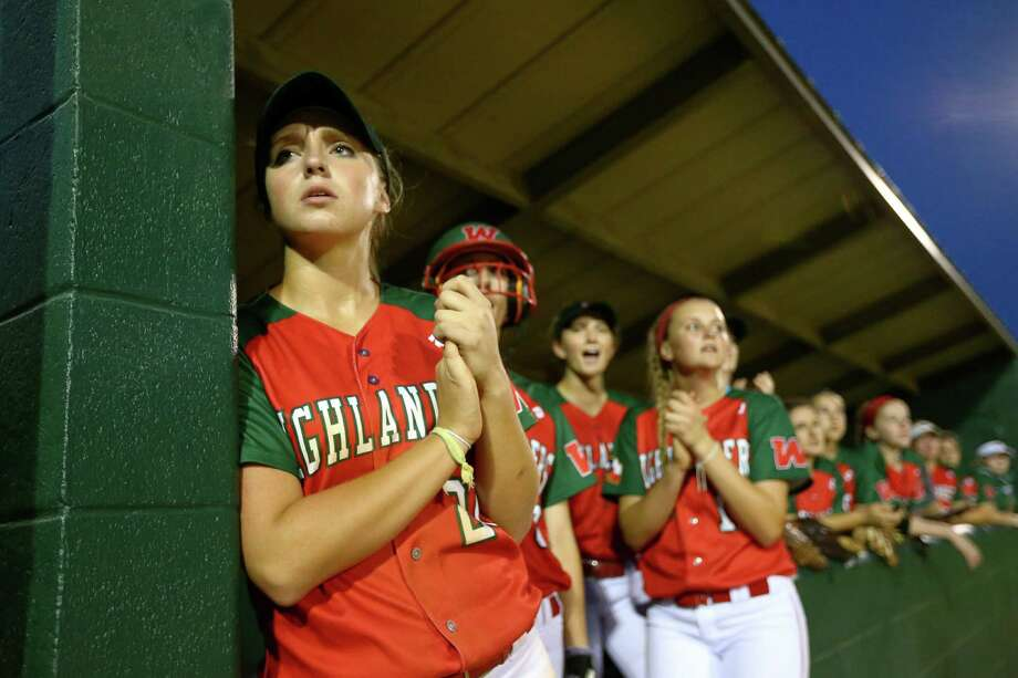 Becca Borstmayer, left, who plays first base, and teammates watch the game between The Woodlands and Kingwood on Friday. In  right photo, Christina Starkweather hugs her daughter Leah after the Lady Highlanders lost to the Mustangs in an emotional game for both teams. Photo: Jon Shapley, Staff / © 2015  Houston Chronicle