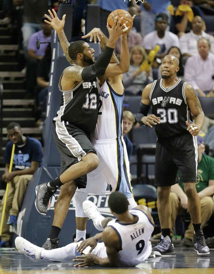 San Antonio Spurs forward LaMarcus Aldridge (12) shoots between Memphis Grizzlies forward Matt Barnes (22) and Tony Allen (9) during the first half of Game 3 in a first-round NBA basketball playoff series Friday, April 22, 2016, in Memphis, Tenn.  Spurs forward David West (30) watches the play. (AP Photo/Mark Humphrey)