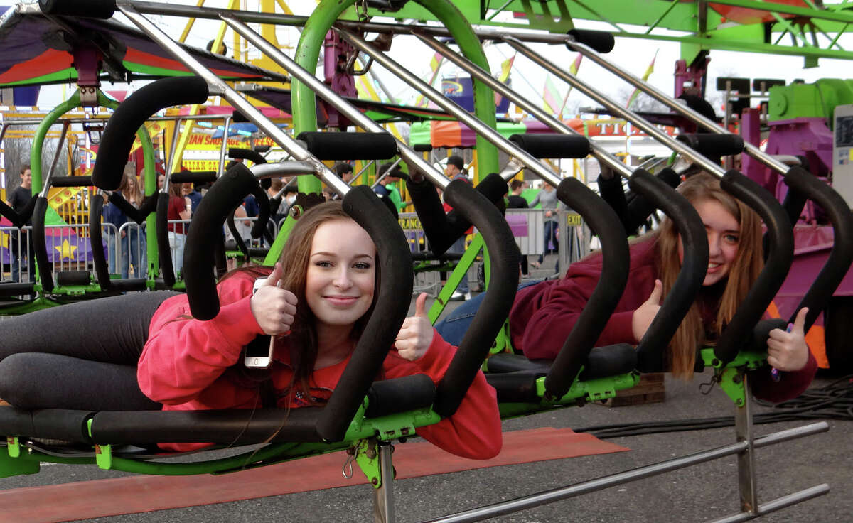 Fairfielders Sally Binswanger, 15, and Bella Phillips, 14, give a thumbs-up from the Cliff Hanger ride at the McKinley School PTA Carnival at Jennings Beach.