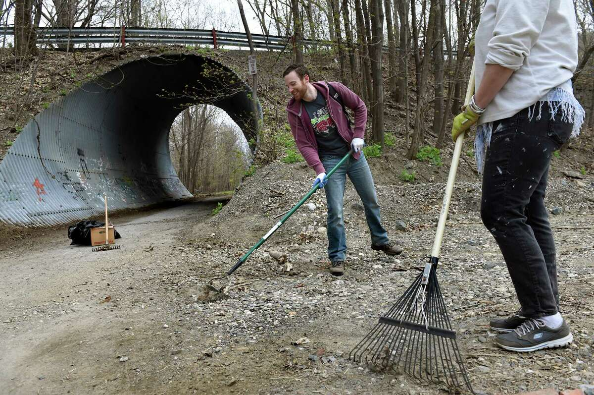 In an Earth Day effort, Will Malcolm of Capital Roots, center, and Barbara Nelson of Transport Troy clean up the Uncle Sam Bikeway on Saturday, April 23, 2016, in Troy, N.Y. The 3.1-mile, paved rail trail that runs through northern Troy is lined with woods, wildflowers, waterfalls and shale cliffs. Capital Roots partnered with other local groups and National Park Rivers and Trails. (Cindy Schultz / Times Union)