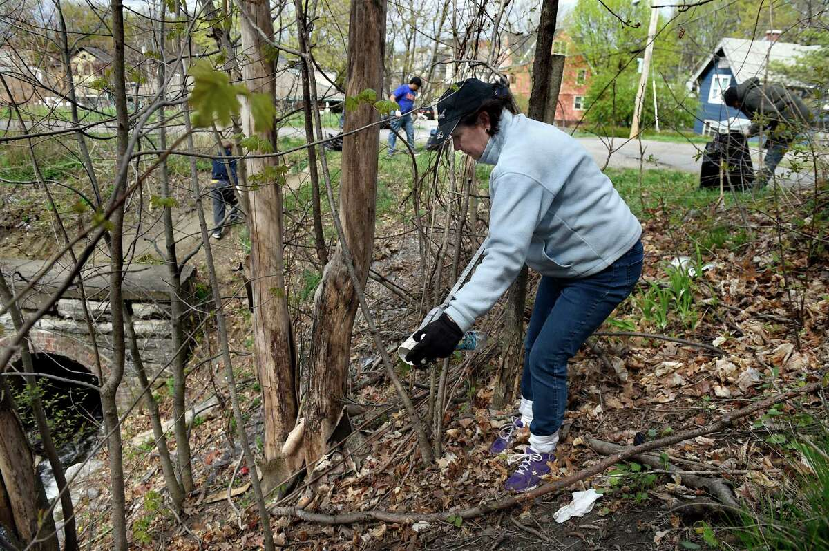 In an Earth Day effort, Robin Stokes of Grace Fellowship cleans up the Uncle Sam Bikeway on Saturday, April 23, 2016, in Troy, N.Y. The 3.1-mile, paved rail trail that runs through northern Troy is lined with woods, wildflowers, waterfalls and shale cliffs. Capital Roots led the effort and partnered with other local groups and National Park Rivers and Trails. (Cindy Schultz / Times Union)