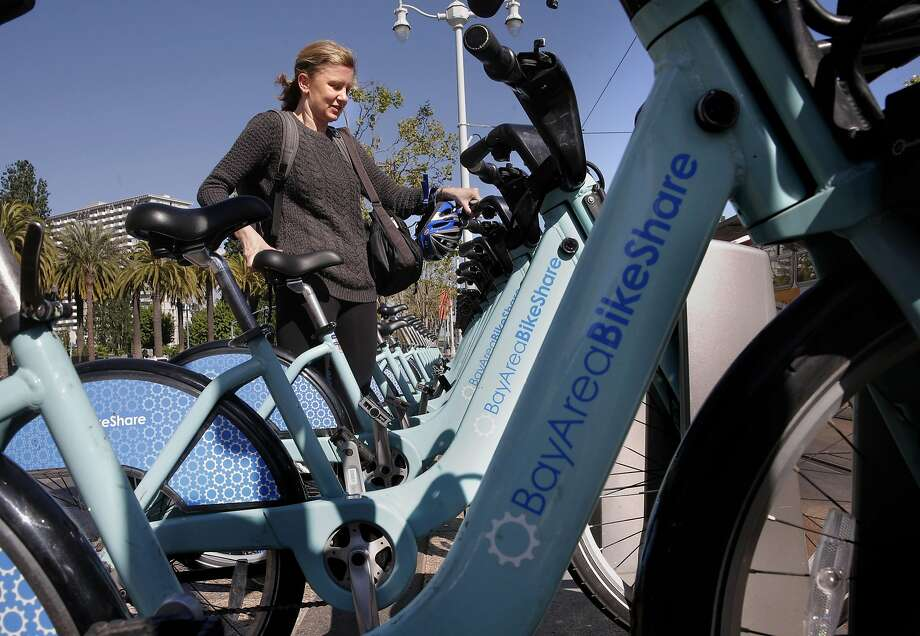 Jenny Kempenich of San Francisco returns a rental bike at the Embarcadero and Ferry building station in San Francisco.  Photo: Michael Macor, The Chronicle