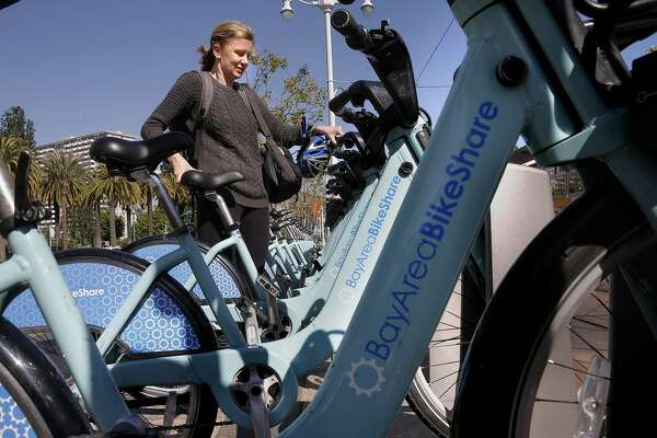 Jenny Kempenich of San Francisco returns a rental bike at the Embarcadero and Ferry building station in San Francisco, California on Sat. April 23, 2016. Bay Area Bike Share is planning to expand into the East Bay adding 1,500 bicycles and 117 new stations.