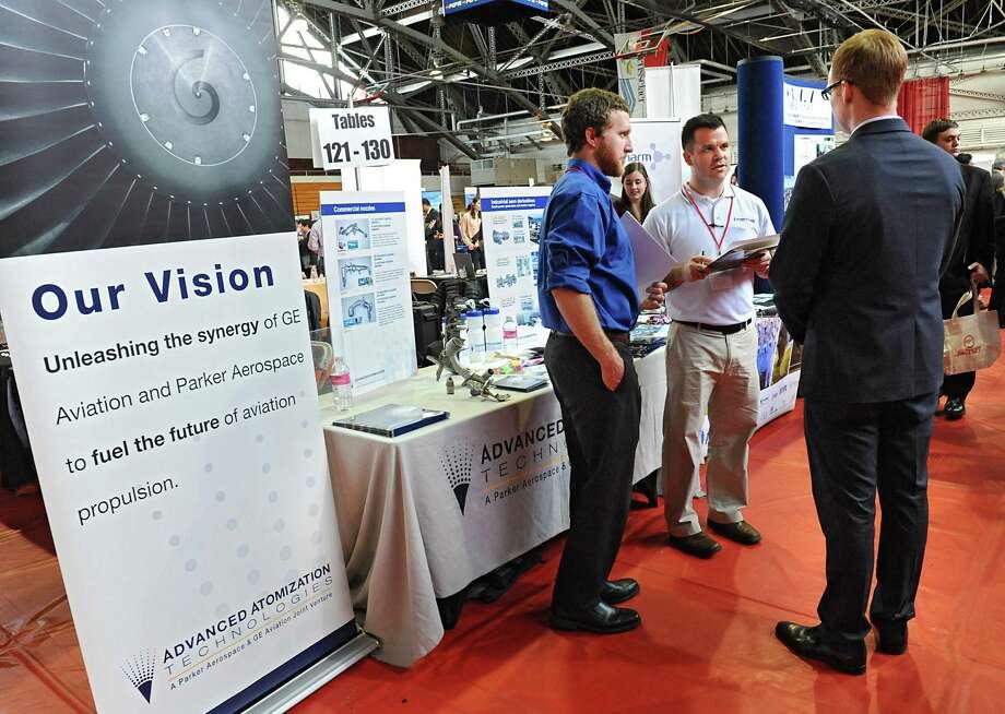 From left, Carl Busta and Jesse Dumar of Advanced Atomization Technologies talk to Rensselaer Polytechnic Institute senior Jeff Daring of Cornell, N.Y. during a job fair at RPI on Wednesday, Feb. 10, 2016 in Troy, N.Y.(Lori Van Buren / Times Union) Photo: Lori Van Buren / 10035354A
