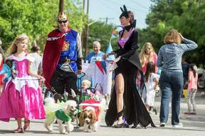 Lilah Noelle Hampton, 6, holds her dogs Oloff, as her dad Ryan Hampton pulls his son Nolan, 2, center,  and her mother Nikole Hampton participate in  the 2016 Fiesta Pooch Parade on Saturday, April 23, 2016.  Carlos Javier Sanchez / For The Express News