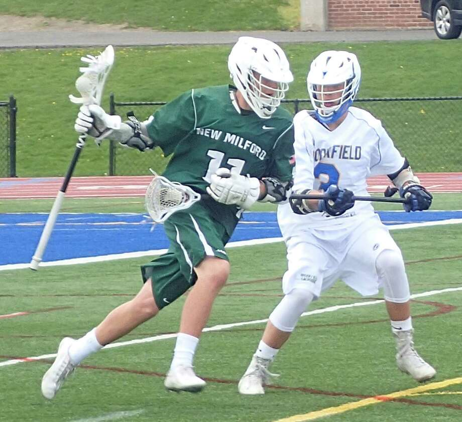 New Milford's Evan Federowicz, left, drives toward the net with the ball as Brookfield's Dom Biasetti defends during the boys lacrosse game at Brookfield High School April 23, 2016. Photo: Richard Gregory / Richard Gregory