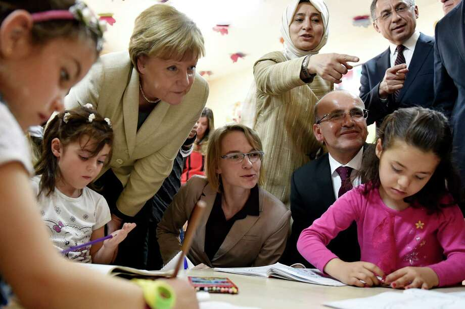 GAZIANTEP, TURKEY - APRIL 23:  In this photo provided by the German Government Press Office (BPA), Turkey's Prime Minister, Ahmet Davutoglu looks on as German Chancellor Angela Merkel speaks to girls in a classroom on April 23, 2016 in Gaziantep, Turkey. Merkel is in Germany to commence the EU aid program for Syrians in Turkey and visit a refugee camp.  (Photo by Steffen Kugler - Pool/Bundesregierung via Getty Images) ORG XMIT: 632442443 Photo: Pool / 2016 Bundesregierung