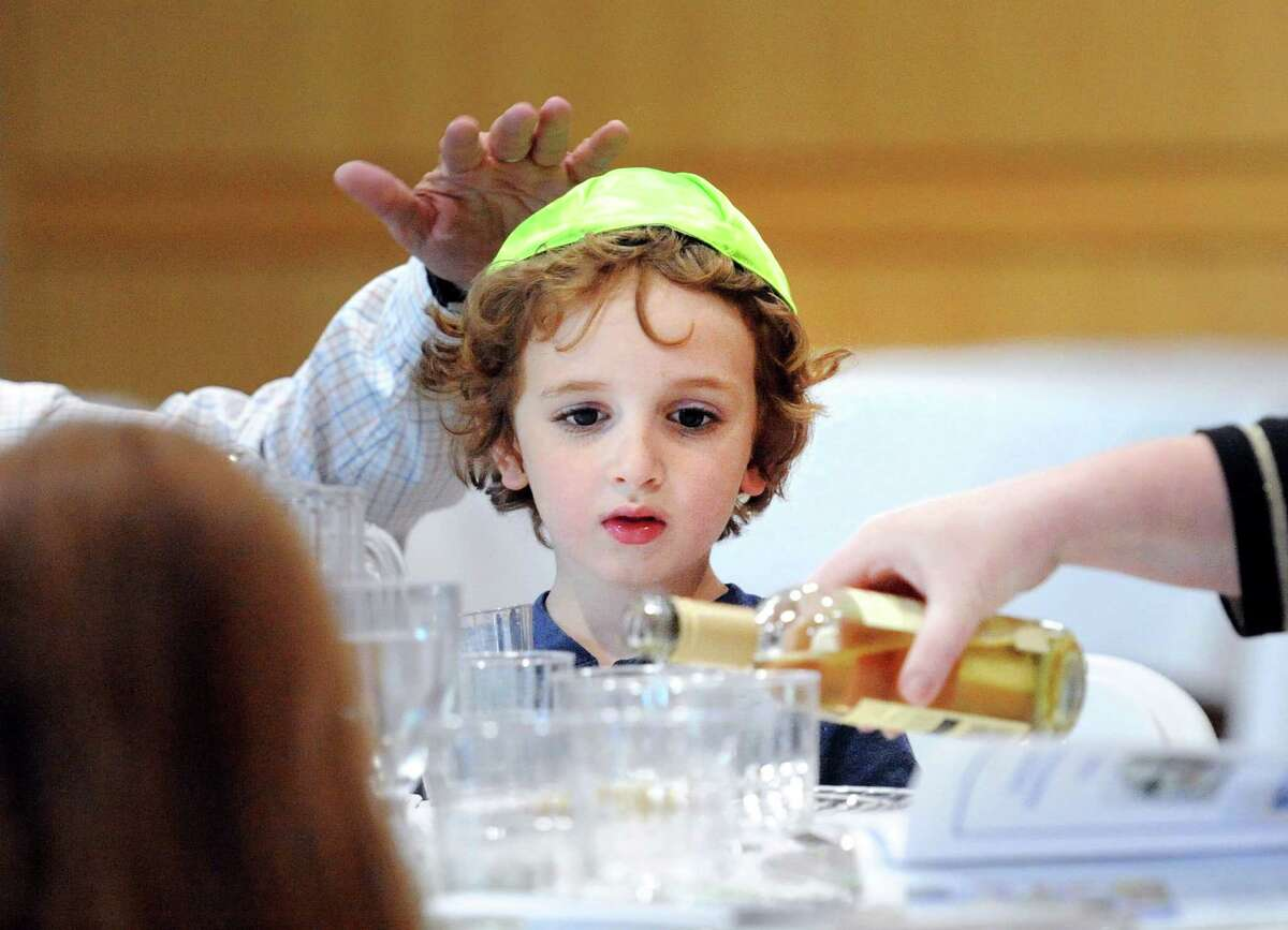 Joe Fulgione, 3, of Greenwich, during the second night Seder service at Temple Sholom in Greenwich, Conn., Saturday, April 23, 2016. The Seder is a festive ritual dinner that involves the retelling of the story of the liberation of the Israelites from slavery in ancient Egypt and is part of the sacred eight-day Jewsih holiday of Passover. The second night Seder was lead by Assistant Rabbi Yoni Nadiv with Cantor Asa Fradkin providing the singing and music. 75 people attended.